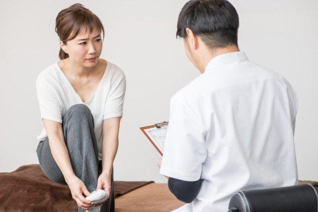 足裏の痛みを訴える女性の写真